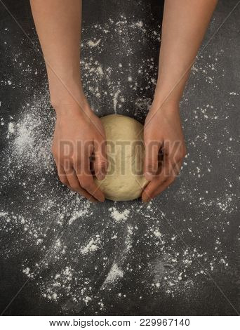 Women's Hands Kneaded Lump Of Dough On Table