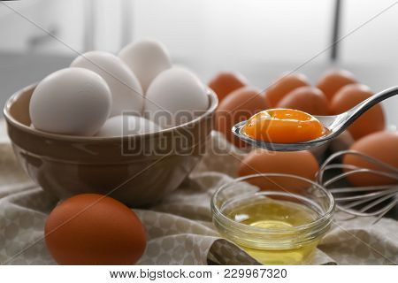 Spoon with egg yolk over glass bowl on table