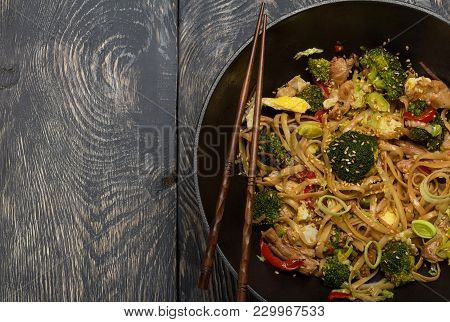 Spicy Dish, Noodles With Meat And Vegetables In Wok Pan, On Dark Wooden Surface