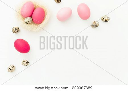 Easter Eggs And Quail Eggs In Nest On White Background, Top View, Fat Lay. Easter Holiday Concept Wi