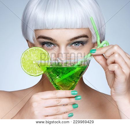 Glamorous Girl With Green Cocktail In Front Of Her Face. Photo Of Fashion Blonde Girl On Blue Backgr