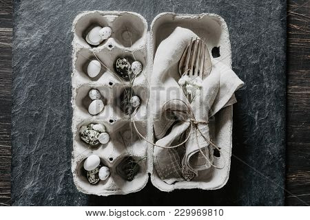 Natural Easter Table Decoration With Silverware And Eggs In Egg Box On Black Stone