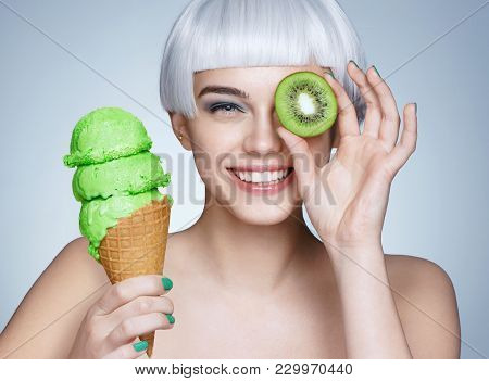 Funny Young Girl Holding Waffle Cone With Ice Cream And Kiwi Fruit. Photo Of Smiling Blonde Girl On