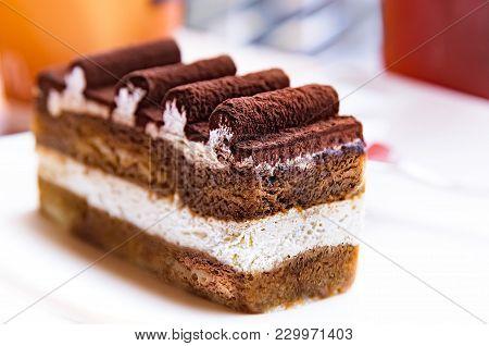 A Slice Of Tiramisu Cake With Cream And Chocolate Roll Icing At Cafe On Summer. Italian Dessert Conc