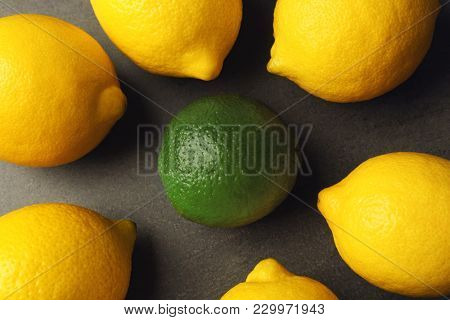 One lime among lemons on gray background. Difference and uniqueness concept