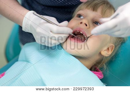 Baby Girl  Visiting Stomatology Clinic. Dentist Making Checkup Of Kids Teeth. Children Tooth And Mou