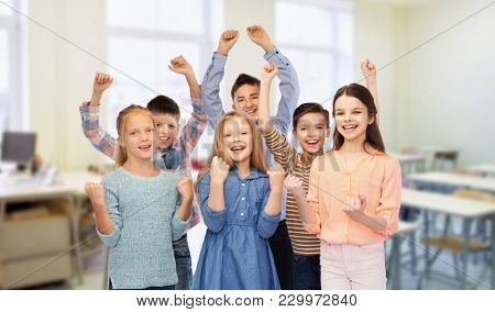education, school, success and people concept - happy students raising fists and celebrating victory over classroom background