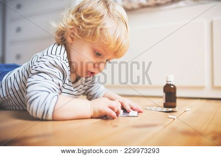 Little Toddler Playing With Pills. Domestic Accident. Dangerous Situation At Home.