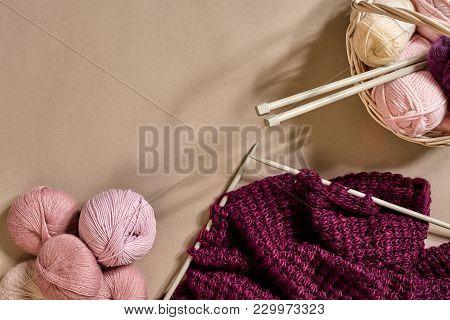 Balls Of Merino Wool Yarn, Knitting On Knitting Needles On A Beige Surface. Pink, White And Purple B