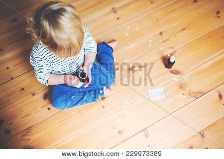 Little Toddler Playing With Pills. Domestic Accident. Dangerous Situation At Home. Top View.