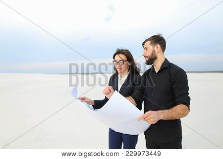 Ceo Male And Cfo Female Holding Whatman Paper, Colleagues Discuss Project Of Wind Power Plant In Des