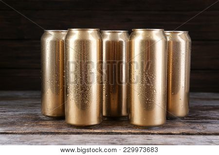 Cans of beer on wooden table against black background