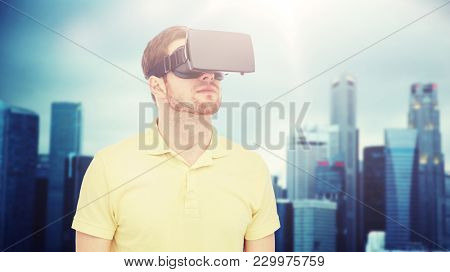 3d technology, virtual reality, entertainment and people concept - young man with virtual reality headset or 3d glasses over singapore city skyscrapers background