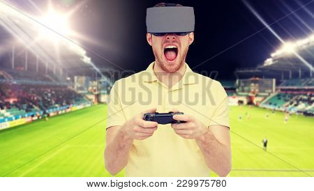3d technology, virtual reality, sport, entertainment and people concept - man in virtual reality headset or 3d glasses playing with game controller gamepad over football field on stadium background