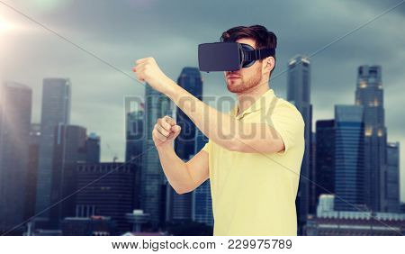 3d technology, virtual reality, entertainment and people concept - young man with virtual reality headset or 3d glasses playing game and fighting over singapore city background