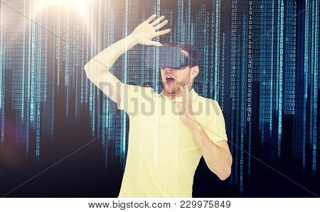 3d technology, virtual reality, entertainment and people concept - scared young man with virtual reality headset or 3d glasses playing game over binary code background