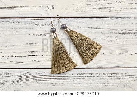 Beige Tassel Earrings On White Wooden Background