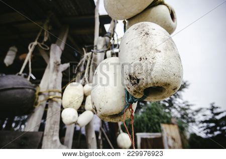 Close Up And Selective Focus. Group Of Dirty White Fish Net Buoy Tied With Rope, Hanging Under Woode