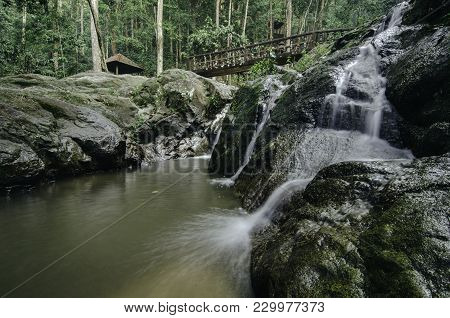 Small Waterfall Surrounded By Green Nature Forest And Mossy On The Rock. Concrete Bridge Crossing Th
