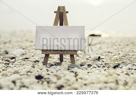Vantage Look Image Of White Canvas On Wooden Tripod With Clam Shell Background During Sunset.