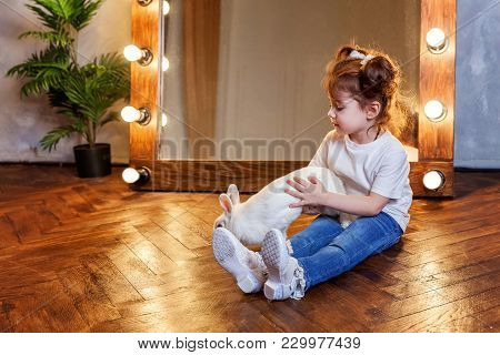 Easter Celebration, Pet Care And Animals Concept. Cute Happy Little Girl Sitting On The Floor And Pl