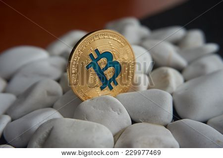 Golden Bitcoin Coin Stuck Between White Stones. Cryptocurrency Mining Concept, Selective Focus.