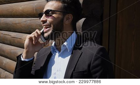 Specialist Holds Phone In Hand And Talking With Boss. Man Stands Near Wooden House. Arabian Guy Has