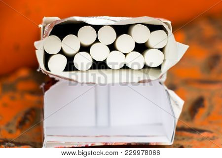 Turn On The Cigarette With A Filter Placed On An Orange Background.