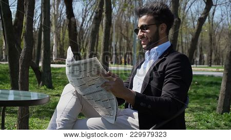 Guy Sits On Chair Near Table And Reading Newspaper. Man Has Beard, Short Hair And Dimples. Male Dres