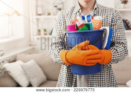 Unrecognizable Man Ready To Clean, Holding Plastic Bucket, Brushes, Sponges And Other Cleaning Equip