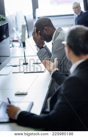 Selective Focus Of Stressed African American Businessman And Arguing Colleague In Office