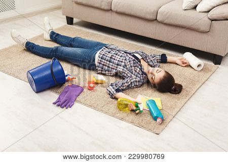 Tired Woman Lying On Carpet After Cleaning Home In The Living-room, Copy Space. Housekeeping And Hom