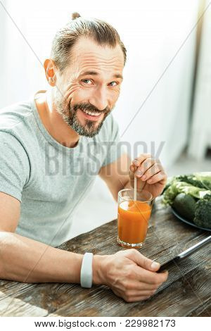 Good Mood. Happy Funny Pleasant Man Sitting By The Table With A Glass Of Juice Smiling And Using The