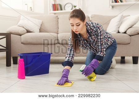 Concentrated Woman Polishing Wooden Floor. Young Girl In Protective Gloves Washing Apartment, Spring