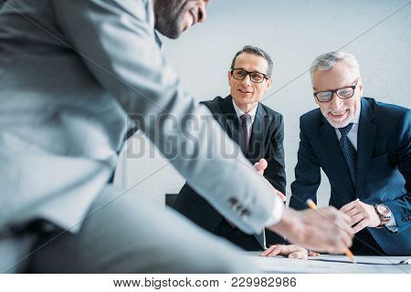 Partial View Of Multiethnic Businessmen Discussing New Business Strategy On Meeting In Office
