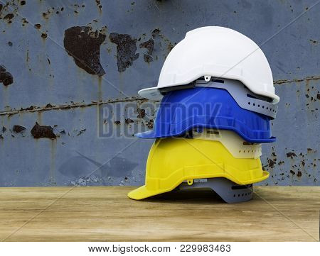 White, Blue And Yellow Helmets Are Placed On The Table. Safety Helmets For A Technician's Safety Pro