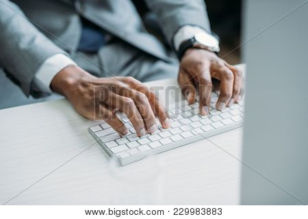 Partial View Of African American Businessman Typing On Keyboard At Workplace