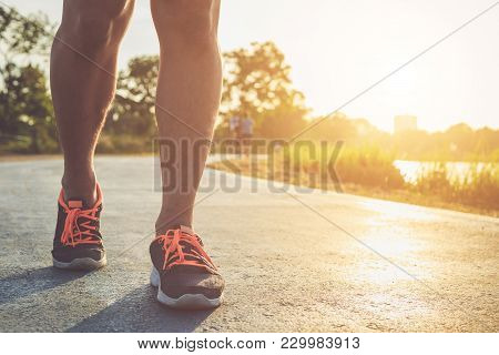 Man Workout Wellness Concept : Runner Feet With Sneaker Shoe Running On Road In The Park. Focus On S