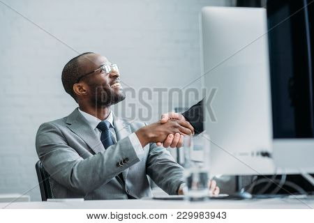 Partial View Of African American Businessman And Colleague Shaking Hands At Workplace