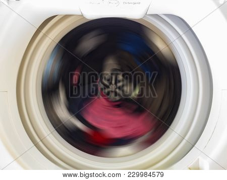 Top View Of A Washing Machine Drum During Spinning Clothes. Top Loading Washing Machine Washes Laund