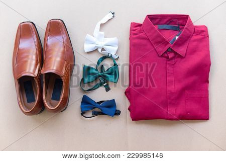 Close Up Of Brown Leather Male Shoes, Three Bow Tie And Red Shirt On Brown Background.  Modern Man O