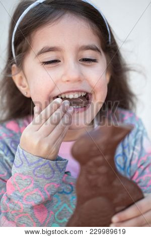 Happy young girl bites off the ear of chocolate Easter bunny