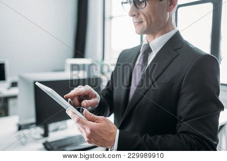 Partial View Of Businessman Using Tablet In Office