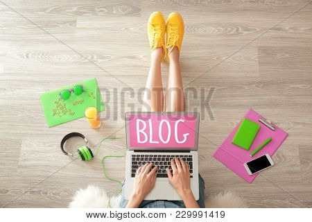 Woman using laptop for visiting blog webpage while sitting on floor