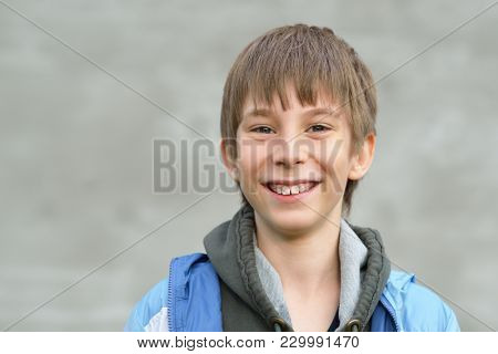 Portrait of attractive happy smiling 11 years old boy, outdoor over gray wall. Happy handsome teenager. Cute kid's portrait.