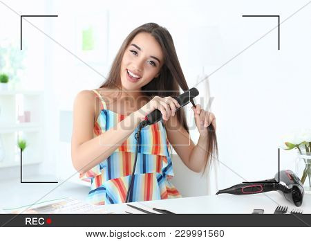 Young blogger styling hair while recording video at home. View of camera screen