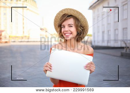 Young blogger with laptop recording video outdoors. View of camera screen