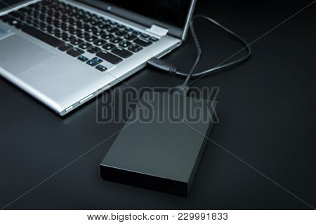 An External Hard Drive  Connected To The Laptop With A Usb Cable On A Black Background. Portable Sto