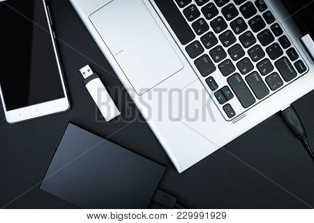 External Hdd Connected To The Laptop, Usb Flash Drive And Smartphone On A Black Background, Top View