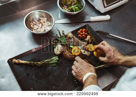 Male Chef Cooking And Serving Juicy Medium Beef Steak And Grilled Vegetables. Healthy Exclusive Food